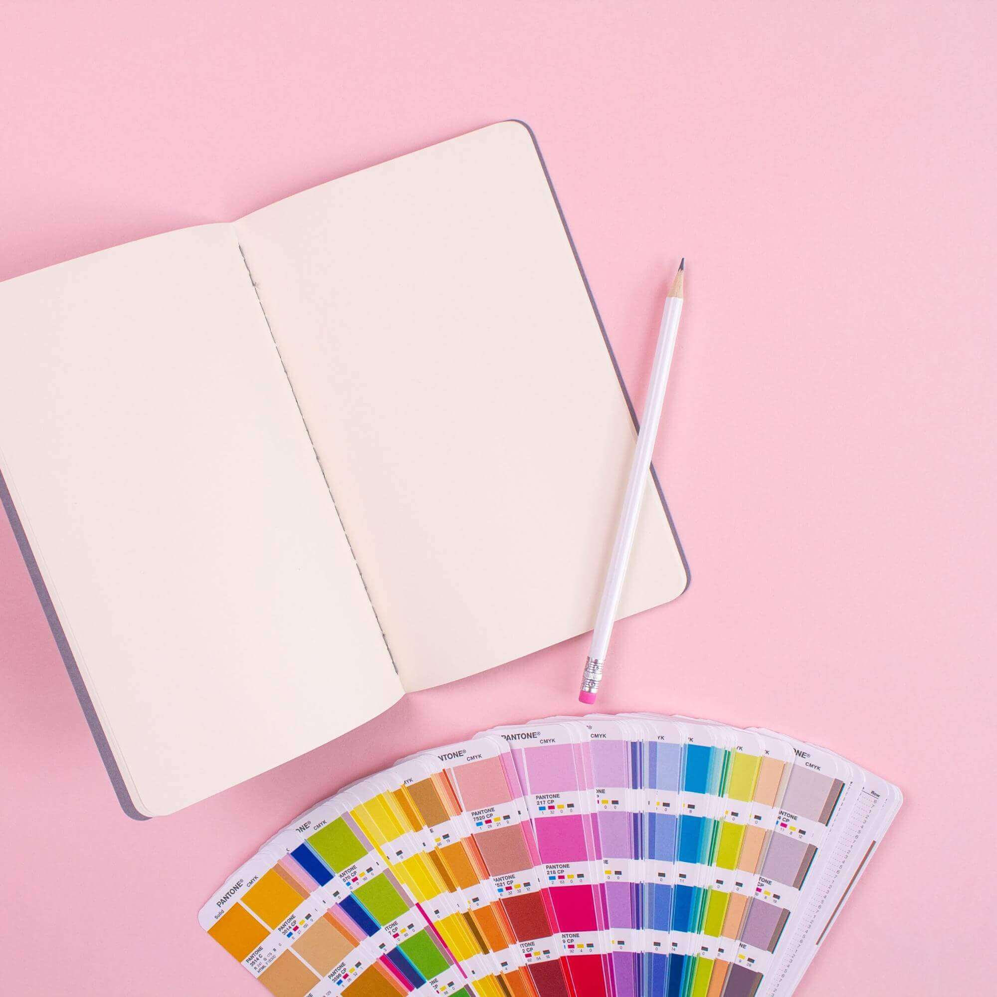 a photo of a notebook, a pencil and a color palette, indicating a design process.
